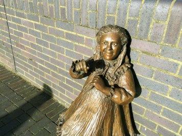 Fragment pomnika Alfreda Saltera - lekarza i społecznika zaangażowanego w poprawę higieny i warunków życiowych w stanowiącej część doków dzielnicy Bermondsey (1. poł. XX w.). Kiedy parę lat temu ukradziono rzeźby, mieszkańcy zorganizowali zbiórkę pieniędzy na nowy pomnik. Dzięki hojnemu wsparciu Dame Judi Dench udało się nie tylko odtworzyć figury doktora, jego żony i tragicznie zmarłej córki, ale dołączył do nich jeszcze kot.