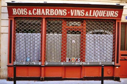 Jedna z ostatnich ocalałych witryn dawnych składów drewna, węgla, win i likierów. Widzieliśmy już taki w Quartier Popincourt. To połączenie może dziwić. Chodzi jednak o składy imigrantów z Owerni, tzw. Bougnats. Początkowo parali się profesją nosiwody. Od XVII wieku zamiast wody, zaczęli dostarczać drewno i węgiel, a później ich oferta poszerzyła się o wina i likiery. Chodzi zatem o bardzo bogatą i ważną dla kultury miasta tradycję.